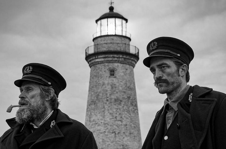 Robert Pattinson and William Dafoe infront of the lighthouse