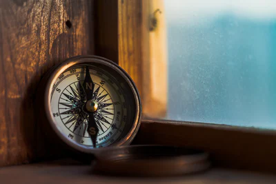 brown, classic compass located on a window sill with a blue background.