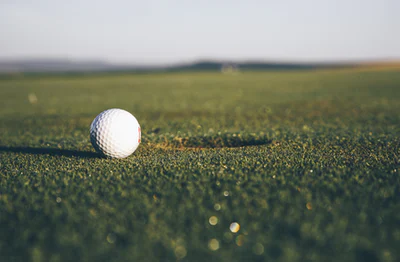 a golf course close u on a golf ball and putter