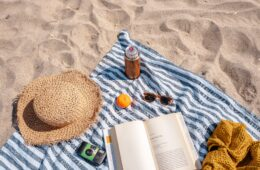 a picnic blanket on a sunny beach with several items that go well for summer and wllness